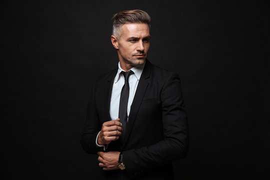 Handsome mature business man posing isolated over black wall background.