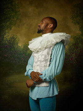 Young man as a medieval grandee or nobleman on dark studio background. Looking serious. Portrait of male model in retro costume. Human emotions, comparison of eras and facial expressions concept.