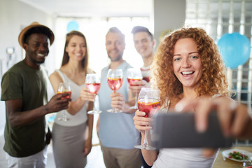 Multi-ethnic group of people smiling cheerfully to camera while posing for selfie photo during party, focus on red haired woman in foreground, copy space