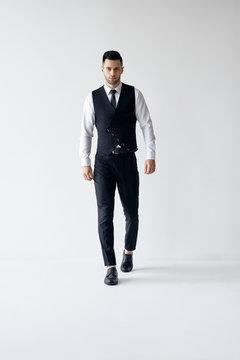Full length portrait of walking elegant man in suit on white background