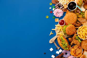 Fototapeta Fast food dish on blue background. Take away unhealthy set including burgers, sauces, french fries, donuts, cola, sweets, icecream and biscuit. Diet temptation resulting in improper nutrition.