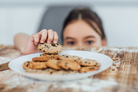 Focus at small girl steals cookie! Home! Bakery!
