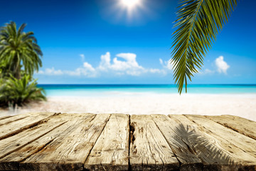 Wooden table background of free space and summer landscape of beach with palms and ocean.