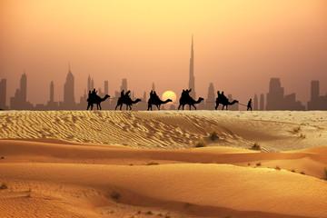 Man and camels in caravan with tourists on sand dunes of Arabian dessert, Dubai skyline seen away