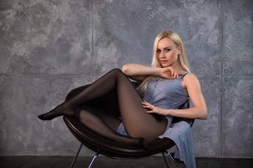 Beautiful blonde girl in pantyhose posing in the chair.