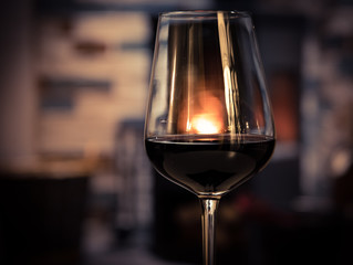 Glass of red wine on cozy fireplace background