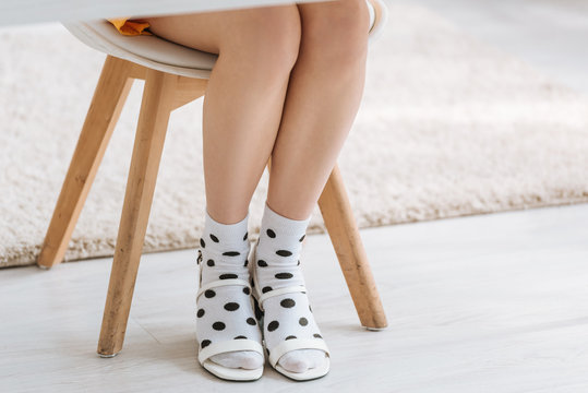 cropped view of young woman in polka dot socks and sandals