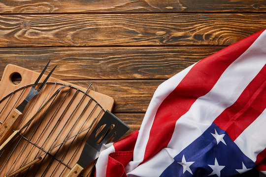 top view of american flag near bbq equipment on wooden rustic table
