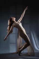 Dancer in a dress for modern dance dancing in the Studio.