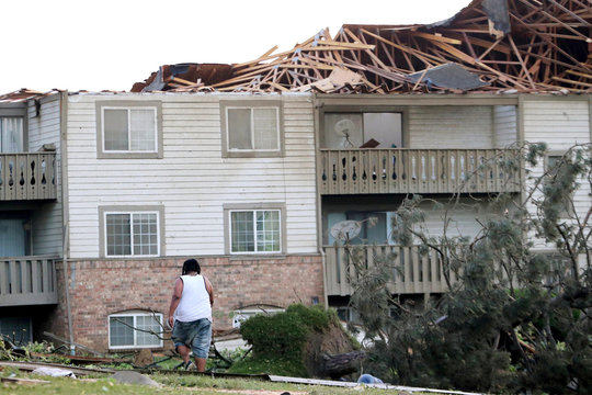 A man walks through the scattered debri outside his apartment building in the morning after a tornado touched down overnight in Trotwood