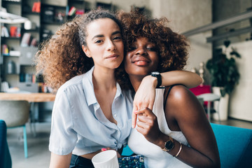 two multiracial friends posing together and looking camera