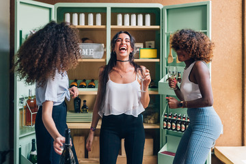 three multiracial women drinking and dancing in modern apartment