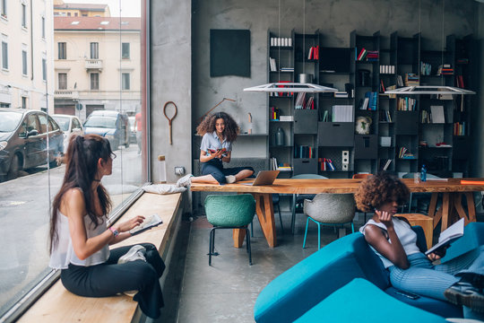 three multiracial young businesswomen working in modern coworking office