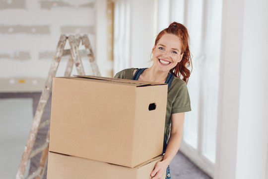 Happy vivacious young woman moving house