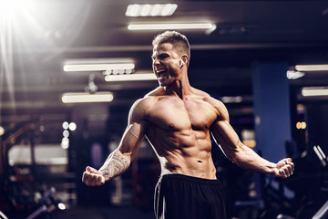 Side view of a caucasian handsome fitness model posing in the gym. Man on diet flexing muscles and six pack abs