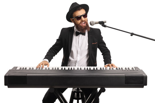 Man with sunglasses and a beard playing a digital piano and singing on a microphone