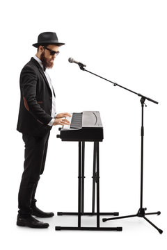 Man standing, playing a digital piano and singing on a microphone