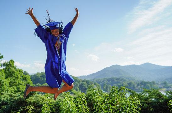 African American American girl graduation jumping for joy