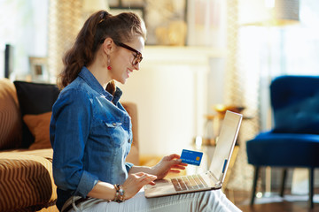 happy young woman making online purchases on laptop