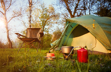 Camping in the woods with a backpack and a tent on the banks of the river .