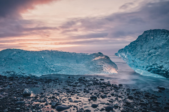 Beautiful sunrise over famous Diamond beach in Iceland. This sand lava beach is full of many giant ice chunks, placed near glacier lagoon Jökulsárlón in southeast Iceland.