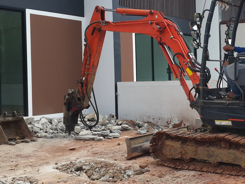 jack hammer tracked bulldozer breaking concrete