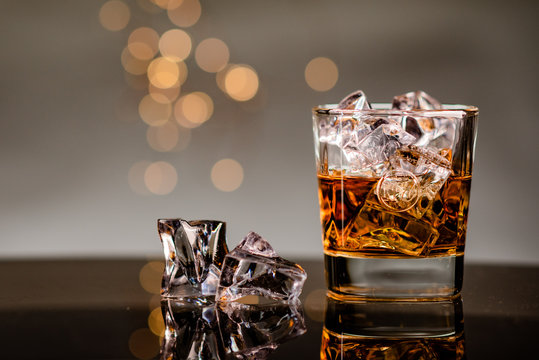 Glass of whiskey on the rocks with ice cubes next to it on a glass table