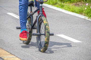 Mini trick stunt bike with camouflage fat tires and pegs being ridden by guy in red tennis shoes and blue jeans on paved surface - cropped and motion blur