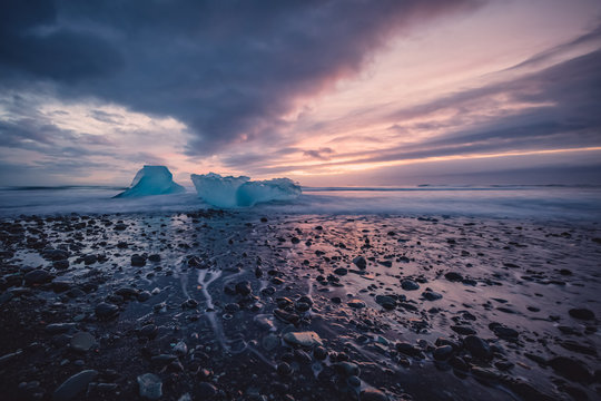 Beautiful sunset over famous Diamond beach in Iceland. This black sand lava beach is full of many giant ice chunks, placed near glacier lagoon Jökulsárlón in southeast Iceland.