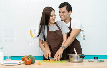 048bdcb0e7 Romantic couple is cooking on kitchen. Young happy smiling couple while  making salad at home