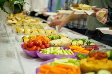 People serving from veggie tray