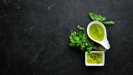Wall Mural - Olive oil and herbs. On a wooden background. Top view. Free space for your text.