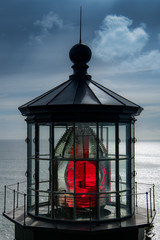 Red light reflecting through the fresnel lens in the cupola of a lighthouse - Cape Mearse Lighthouse on the Oregon coast