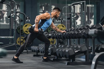 Young bodybuilder taking dumbbells from equipment rack at gym Wall mural