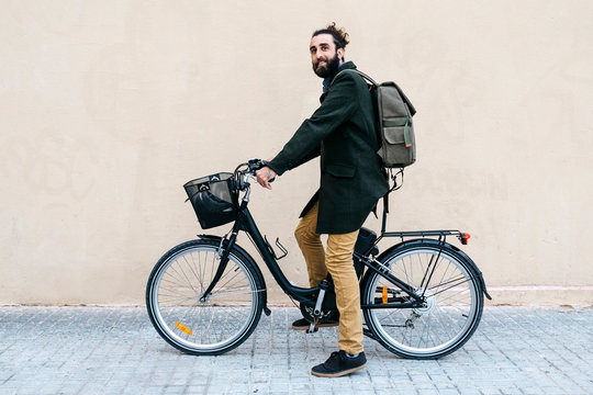 Portrait of smiling man with e-bike at a wall