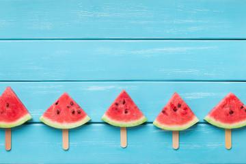 Sliced watermelon on wooden sticks, blue background.