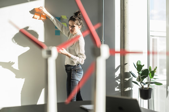 Businesswoman in office putting sticky notes on wall with wind turbine models on desk