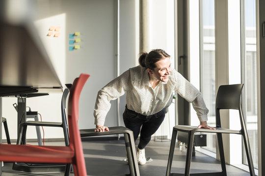 Happy businesswoman exercising in office