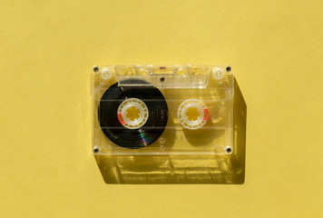 retro transparent audio cassette with copy space for text on yellow background.