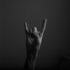 male devil horn rock and roll hand gesture against dark background