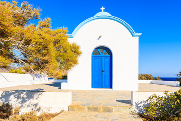 Fototapete - Facade of white typical Greek church with blue door on coast of Karpathos island, Ammopi village, Karpathos island, Greece