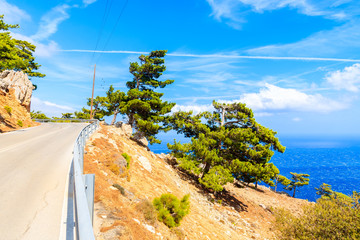Fototapete - Coastal road along sea with high cliffs on Karpathos island, Greece