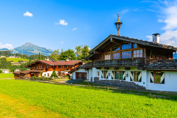 Wall Mural - Typical alpine houses in countryside landscape near Kitzbuhel town, Tirol, Austria