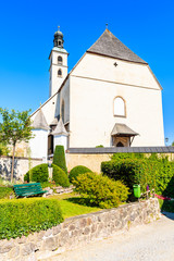 Wall Mural - Church building in Kitzbuhel town against sunny blue sky in summertime, Austria.
