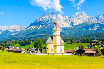 Wall Mural - Church on green meadow in Going am Wilden Kaiser village on beautiful sunny summer day, Tirol, Austria