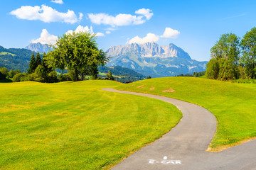 Wall Mural - Way for electric cars on green golf course area against mountains background on sunny summer day, Kitzbuhel, Tyrol, Austria