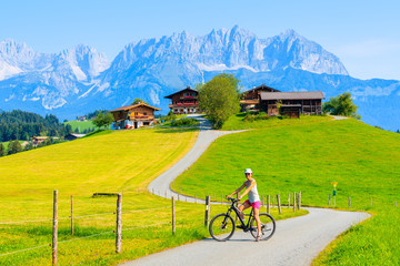 Wall Mural - Young woman tourist riding bike in mountains near Kitzbuhel on sunny summer day, Pertisau, Tirol, Austria