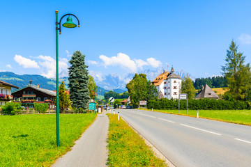 Wall Mural - REITH BEI KIZBUHEL, TIROL - AUG 3, 2018: Road village with alpine houses on green meadow in on sunny summer day, Tirol, Austria.