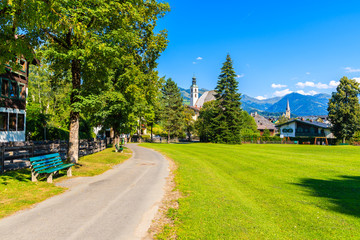 Wall Mural - Path in Kitzbuhel town park with church towers in distance in summertime, Tirol, Austria