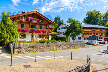 Wall Mural - Street with traditional alpine houses in village of Going am Wilden Kaiser on beautiful sunny summer day, Tirol, Austria